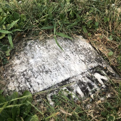 A piece of Henry Freeman's headstone embedded in the ground.